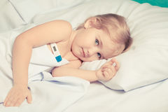 Sick little girl in bed. Stock Photography