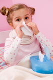 Sick little girl blowing  nose Stock Photography
