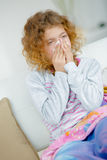 Sick little girl blowing nose Royalty Free Stock Images