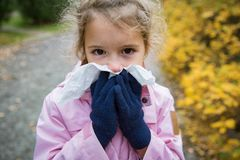 Sick little girl with cold and flu standing outdoors. royalty free stock photos