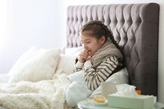 Sick little girl with cough suffering from cold. In bed stock images