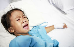 Sick little girl crying in hospital bed Stock Photo