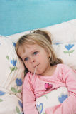 Sick little girl with fever thermometer. A girl is laying in bed, having her temperature checked with an oral fever thermometer, looking miserable Royalty Free Stock Photography