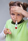 Sick little girl with pills and thermometer Stock Image