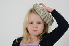 Sick little girl with icebag on head. Sick little blonde girl with pouting lips holds ice bag on head and looks sad Royalty Free Stock Photo