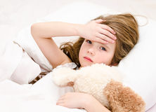 Sick little girl lying in the bed. With her toy Stock Image