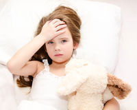 Sick little girl lying in the bed. With her toy Stock Photos
