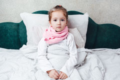 Sick little girl lying in the bed in pink scarf Stock Photo