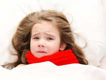 Sick little girl lying in the bed in red scarf Royalty Free Stock Photo