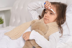 Sick little girl lying in the bed Stock Photos