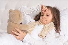 Sick little girl lying in the bed Stock Photography
