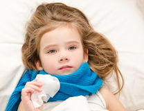 Sick little girl lying in the bed with scarf and tissue. For blowing nose Stock Photos