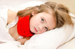 Sick little girl lying in the bed. With thermometer Stock Image