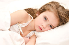 Sick little girl lying in the bed. With thermometer stock photography