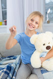 Sick little girl with pale face smiling sitting on couch. Child holding teddy bear in one hand and thermometer in another stock images