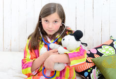 Sick little girl playing with her teddy Royalty Free Stock Photography