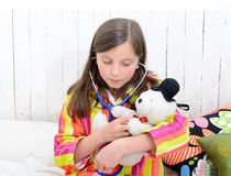 A sick little girl playing with her teddy Royalty Free Stock Photography