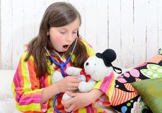 A sick little girl playing with her teddy Stock Image