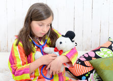 A sick little girl playing with her teddy Royalty Free Stock Photos