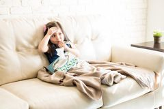 Sick little girl relaxing on sofa. Portrait of little girl suffering from a cold having thermometer in her mouth and holding a box of tissues on sofa in living Royalty Free Stock Photos