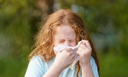 Sick little girl sneeze in handkerchief on outdoors royalty free stock photography