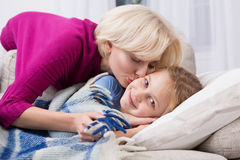 Sick little girl staying at home, mom kissing her. Stock Photo