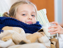 Sick little girl suffering of cold and lying in bed Royalty Free Stock Images