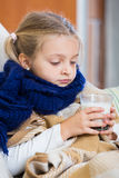 Sick little girl suffering of cold and lying in bed Stock Photo
