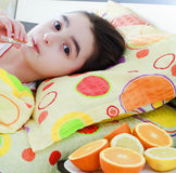 Sick little girl with a thermometer in bed. Sick little 7 years old girl with a thermometer in bed royalty free stock image
