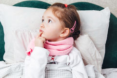 Sick little kid lying in the bed in pink scarf Royalty Free Stock Photography