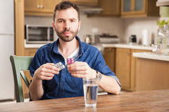 Sick looking man taking some medicine. Portrait of a young man looking ill and taking some pills with a glass of water at home royalty free stock photography