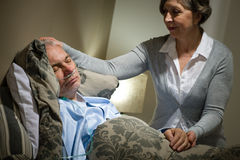 Sick lying senior man and caring wife Stock Images