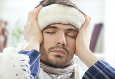 Sick male with wet towel. On his forehead to reduce high fever Stock Image