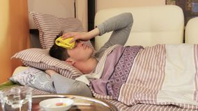 Sick male with wet towel on forehead. Compress. A sick male sleeping with wet towel on his forehead to reduce high high fever stock video footage