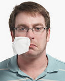 Sick man. Sick young man with a tissue hanging from nose Royalty Free Stock Photography