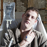 Sick man. Very sick man, with an IV drip sitting in a chair Stock Photos