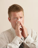 Sick man. Young business man sick blowing nose on tissue Stock Images