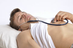 Sick man. Lying in bed checking his own heart with stethoscope Stock Photo