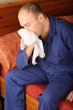 Sick man. Wearing blue pyjamas sat on bed blowing nose with handkerchief Royalty Free Stock Photo