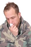 Sick man. One sick adult man with tissues wrapped in a blanket over white Royalty Free Stock Images