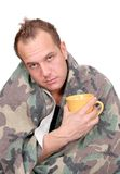 Sick man. One sick adult man holding a mug wrapped in a blanket over white Stock Photo
