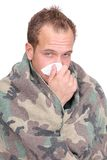 Sick man. One sick adult man with tissues wrapped in a blanket over white Stock Photography