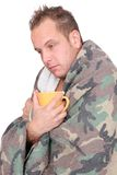 Sick man. One sick adult man holding a mug wrapped in a blanket over white stock images