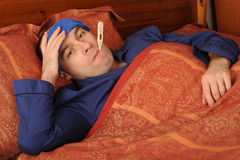 Sick man in bed. With thermometer in mouth Royalty Free Stock Image