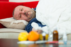 Sick man in bed with drugs and fruit on table Royalty Free Stock Photos