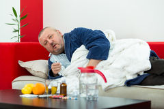 Sick man in bed with drugs and fruit on table Stock Photo