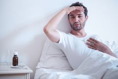 Sick man in bed measuring temperature and feeling bad Royalty Free Stock Photos