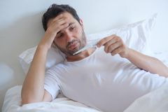 Sick man in bed measuring temperature and looking thermometer. Sick man in bed measuring temperature feeling fever royalty free stock photography