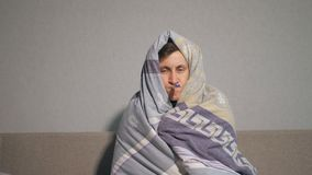 Sick man in blanket taking temperature. Unhappy young man wrapping in warm blanket and keeping electronic thermometer in mouth while suffering from illness at stock video
