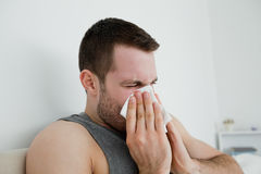 Sick man blowing his nose Stock Images